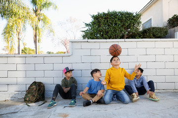 Latinx boys with basketball on sidewalk Fotomurales