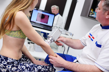 The doctor examines neoplasms or moles on the patient's skin - a young girl using a special apparatus for dermatoscopy - a dermoscope. Prevention of melanoma and skin cancer.