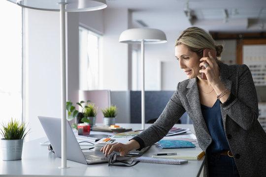 Female interior designer talking on smart phone at laptop in office