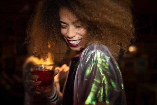 Happy young woman drinking cocktail in nightclub