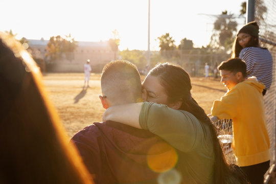 Happy, affectionate mother and son hugging at baseball game