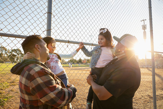 Latinx fathers and daughters behind sunny fence at baseball game