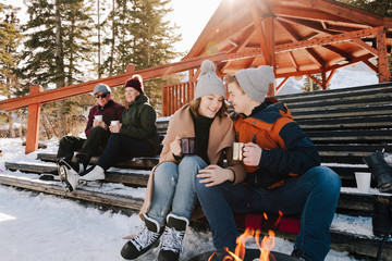Affectionate teenage couple drinking hot cocoa, taking a break from ice skating