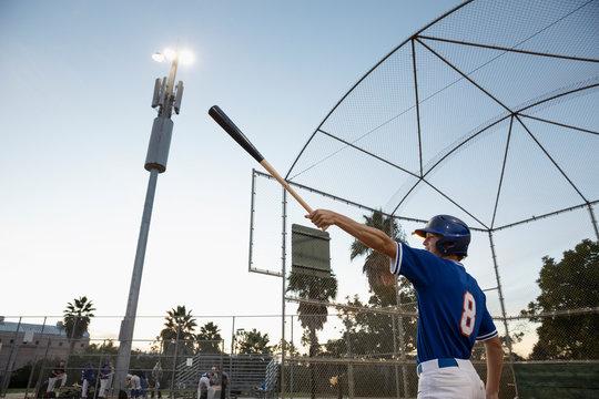 Baseball player swinging bat on field at night