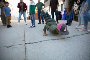Family watching boy break dancing in alley Fotomurales