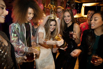 Bachelorette and friends popping champagne bottle at party