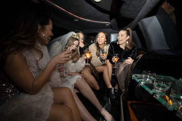 Portrait confident bachelorette and friends drinking champagne in limousine