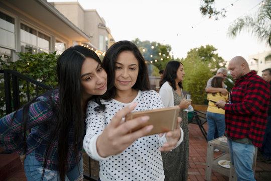 Latinx women taking selfie with smart phone on patio