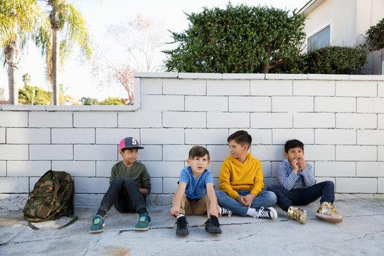 Latinx school boys sitting on sidewalk