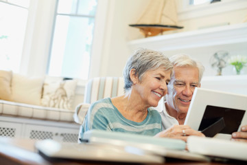 Happy senior couple looking at picture in living room