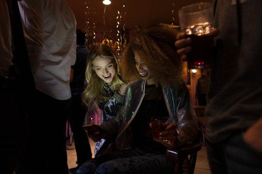 Young women friends using smart phone in dark nightclub