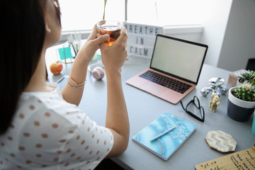 Serene businesswoman drinking tea at desk