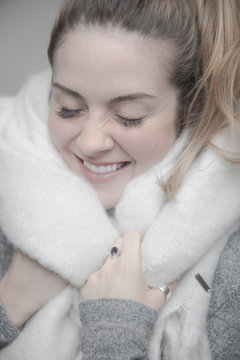 Portrait carefree young blonde woman wrapped in warm blanket