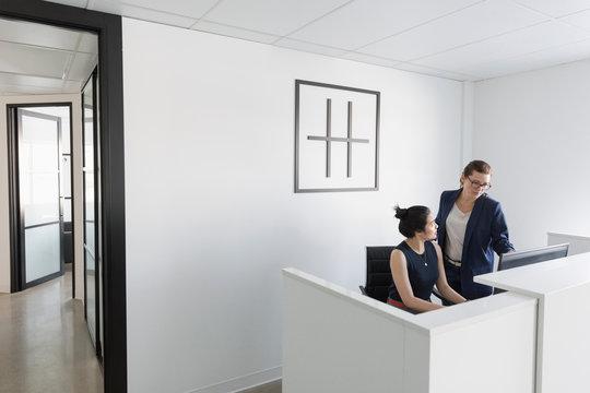 Businesswomen using computer at office reception desk
