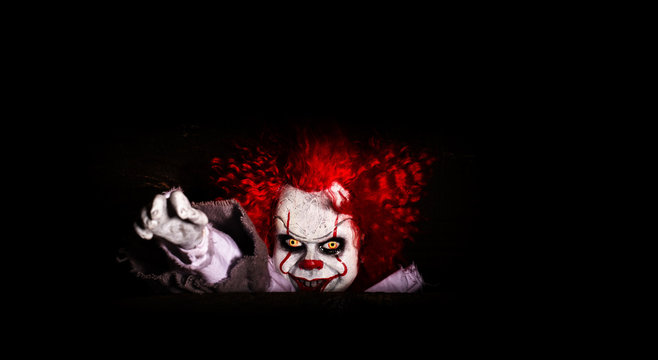the evil clown killer peeps out of cover. horror. halloween concept. evil look.