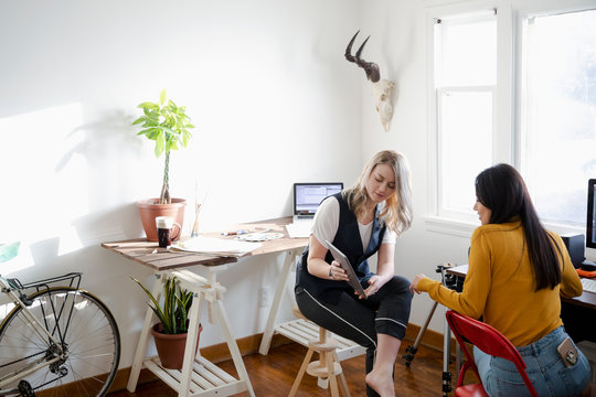 Women with digital tablet working in home office