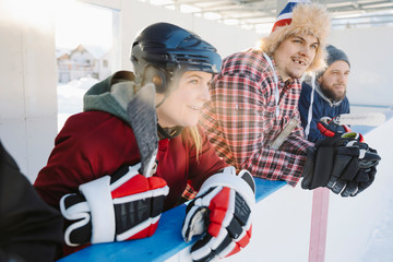 Friends watching outdoor ice hockey match from sideline bench