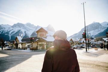Man walking on sunny street in winter mountain town