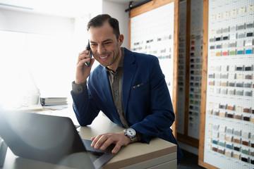 Male interior designer talking on cell phone at laptop in design studio