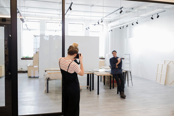 Woman with camera photographing male art gallery owner