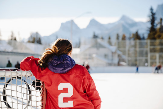 Girl playing outdoor ice hockey, resting on goal