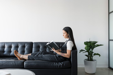 Businesswoman reading book on leather sofa