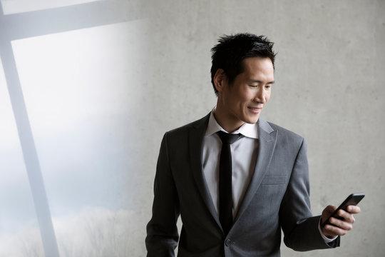 Smiling businessman using smart phone