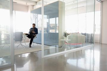 Businessman using digital tablet in modern conference room Fotobehang