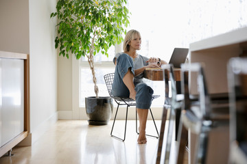 Woman working from home, using laptop at dining table