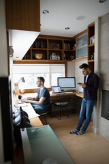 Male gay couple working from home, using laptop and smart phone in home office
