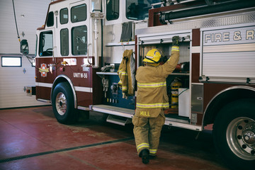Firefighter checking equipment on fire engine