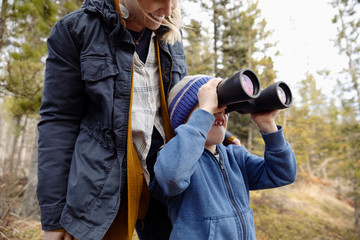 Mother and son with binoculars bird watching, hiking in woods