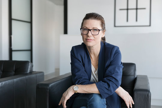 Portrait confident businesswoman sitting in leather armchair in office lobby