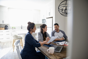 Financial advisor meeting with couple at dining table