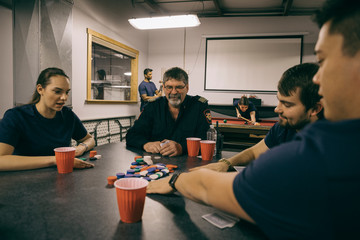 Firefighters playing poker at table in fire station
