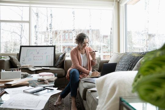 Senior female interior designer working from home, using laptop and smart phone on living room sofa