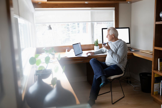 Senior man working at home, using laptop in home office