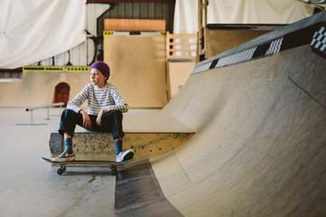 Teenage boy with skateboard sitting at ramp at indoor skate park