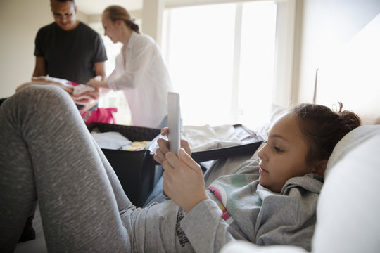 Girl using digital tablet on bed while parents pack suitcases for vacation