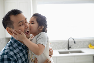 Affectionate daughter kissing father in kitchen