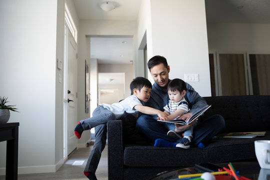 Father and toddler children reading book on living room sofa