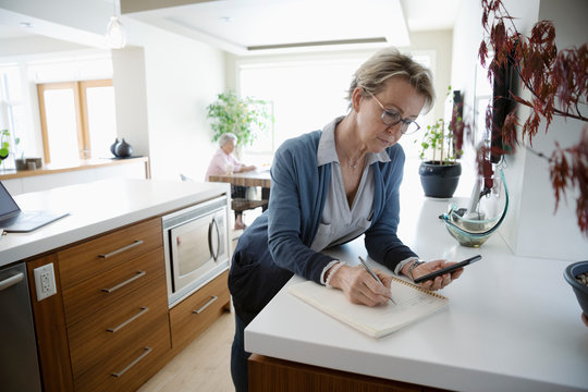 Mature woman with smart phone working from home, writing in notebook in kitchen