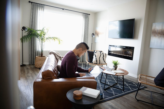 Man working from home at laptop on living room sofa
