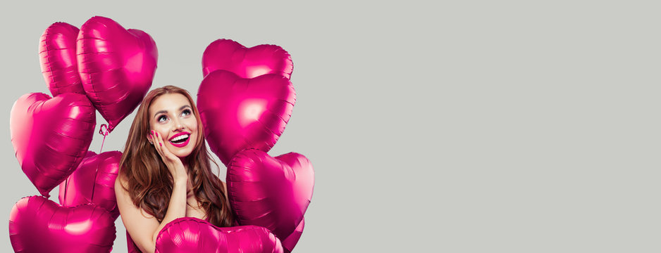 Young model woman having fun and holding pink heart balloons on gray background