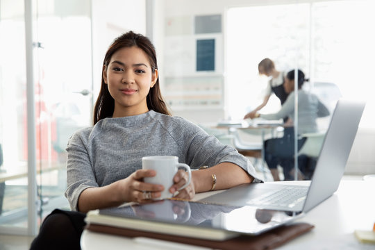 Portrait confident businesswoman drinking coffee at laptop in office