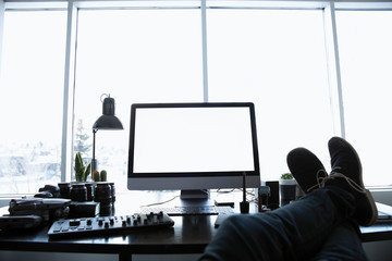Personal perspective male photographer with feet up on desk