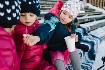 Cute toddler sisters eating on snowy steps
