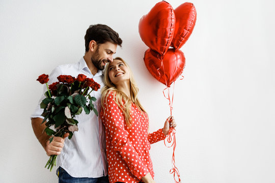 Couple. Love. Valentine's day. Emotions. Man is giving heart-shaped balloons to his woman, both smiling; on a white background