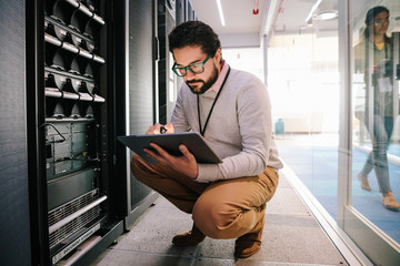 Male IT technician with digital tablet working in network server room