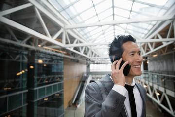 Smiling businessman talking on smart phone on office atrium balcony